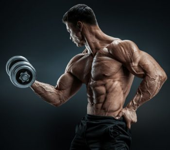 Handsome power athletic man in training pumping up muscles with dumbbell. Strong bodybuilder with six pack, perfect abs, shoulders, biceps, triceps and chest